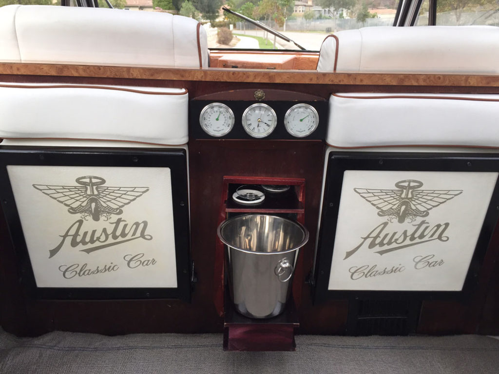 Wooden partition and champagne bucket inside white London Taxi