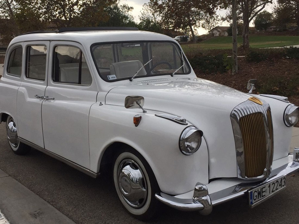 Full exterior view of white London Taxi