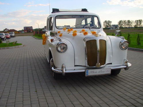 White '92 Convertible London Taxi with flowers on the hood