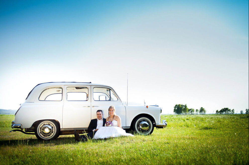 Newlyweds sitting on grass with backs against side of white London Taxi