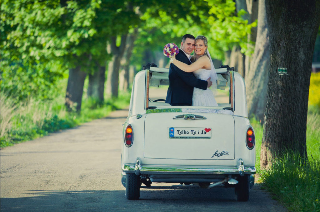 Newlyweds standing in an embrace in back of London taxi with convertible top open