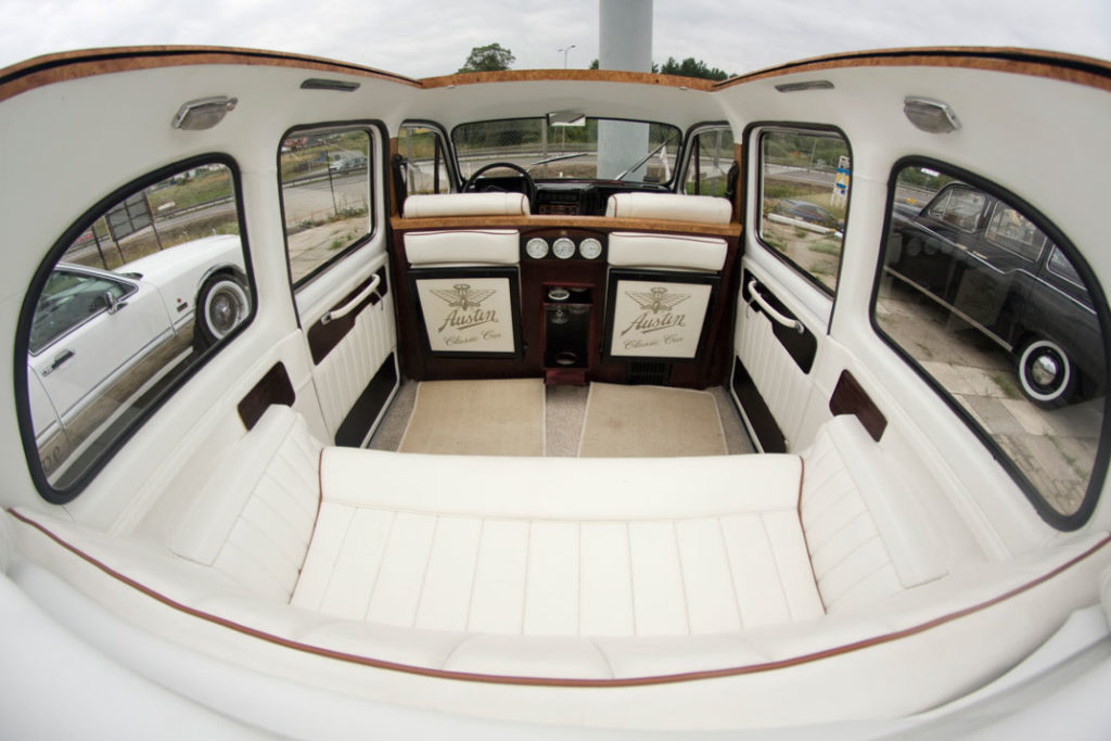 Daytime shot of interior of white London Taxi with convertible top open