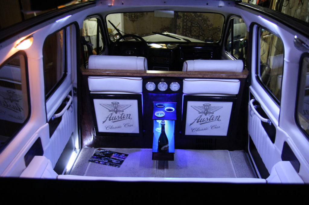 Night shot of interior of white London Taxi with convertible top open