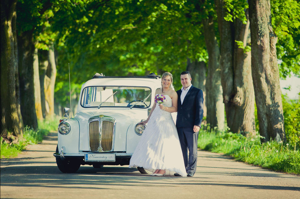 Bride and groom at front of white London Taxi