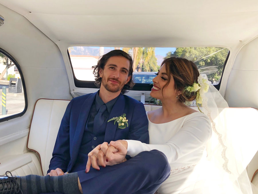 Newlyweds sitting in back of taxi carriage holding hands